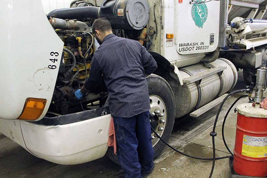 alt=man completing preventative truck maintenance